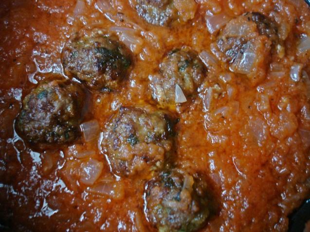 meatballs simmering in sauce.